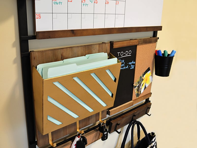 close up of gold colored file holder & chalk board of wall command center