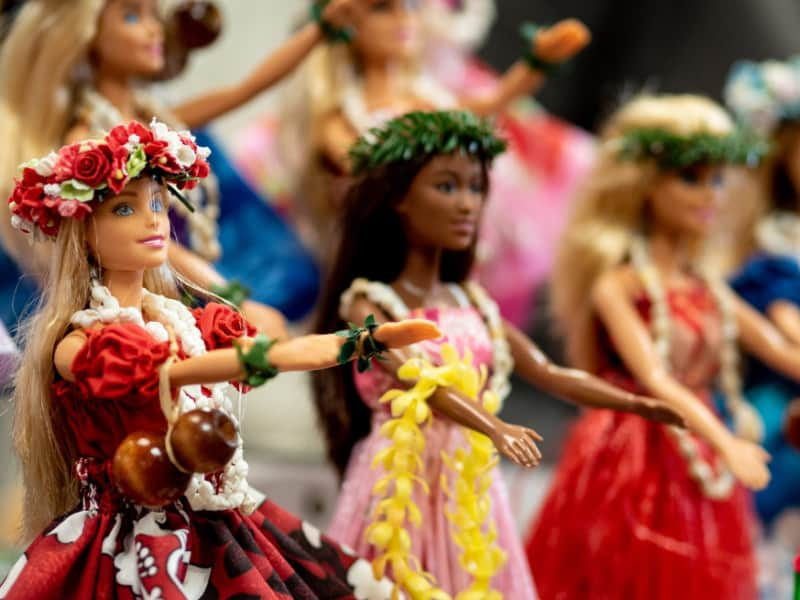 Barbies lined up with arms extended and wearing colorful dresses
