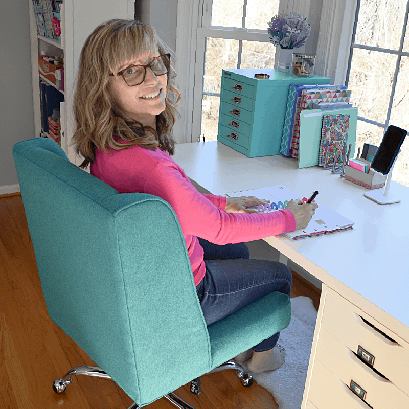 woman in pink shirt sitting in blue desk chair looking back at camera and smiling