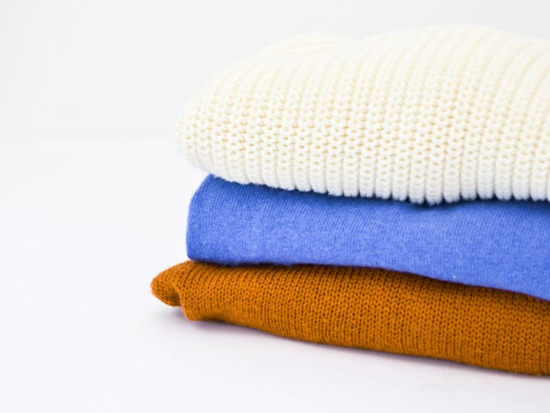stack of 3 folded sweaters