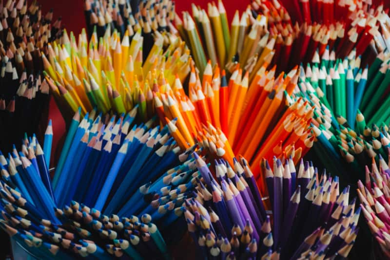colored pencils organized by color in jars