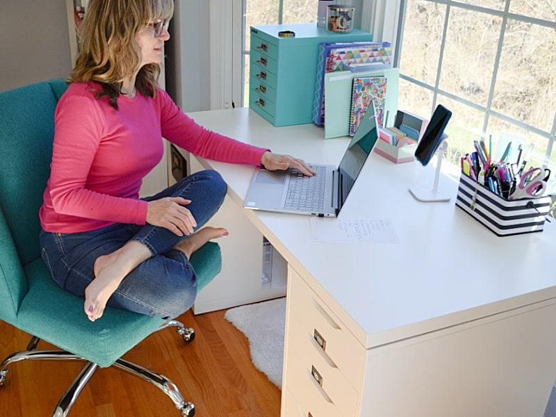 woman sitting cross legged on blue desk chair