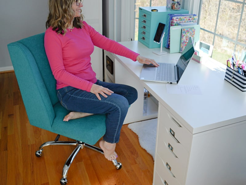 woman sitting in blue desk chair at desk