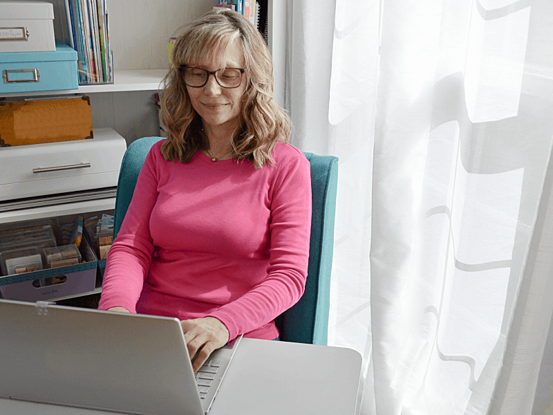 woman in pink shirt sitting at desk