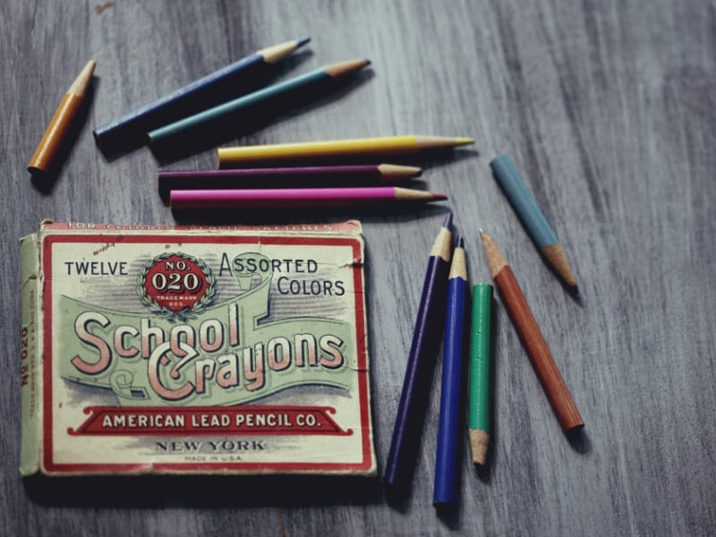 colored pencils on table next to pencil box