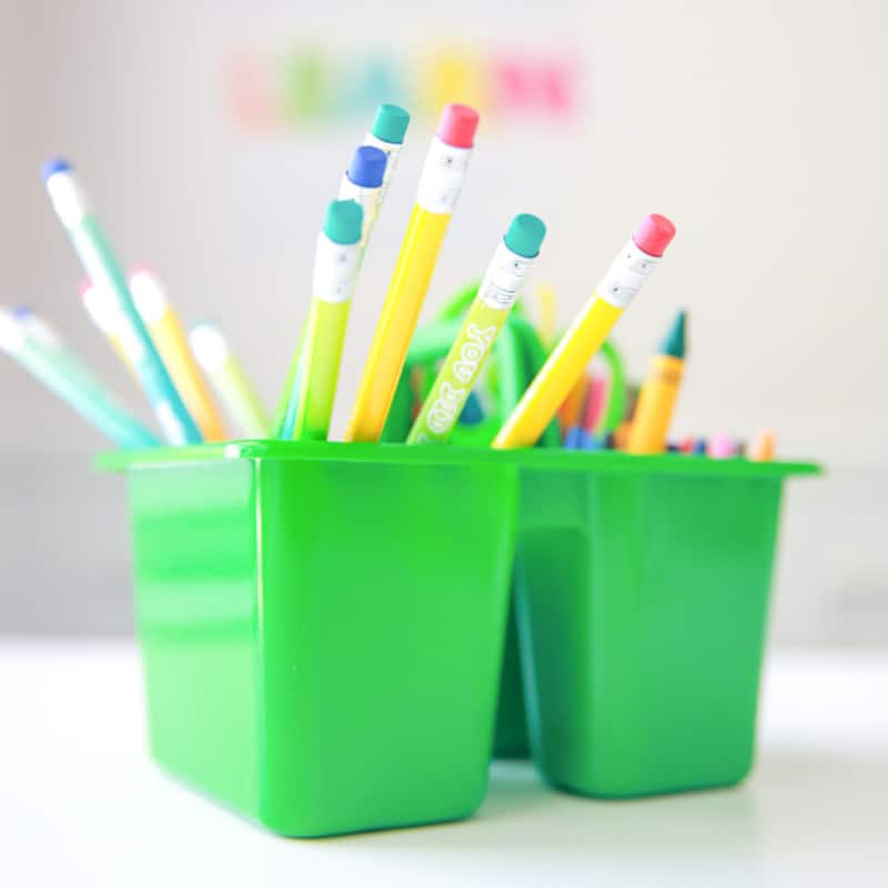 colorful pencils in green caddy on table