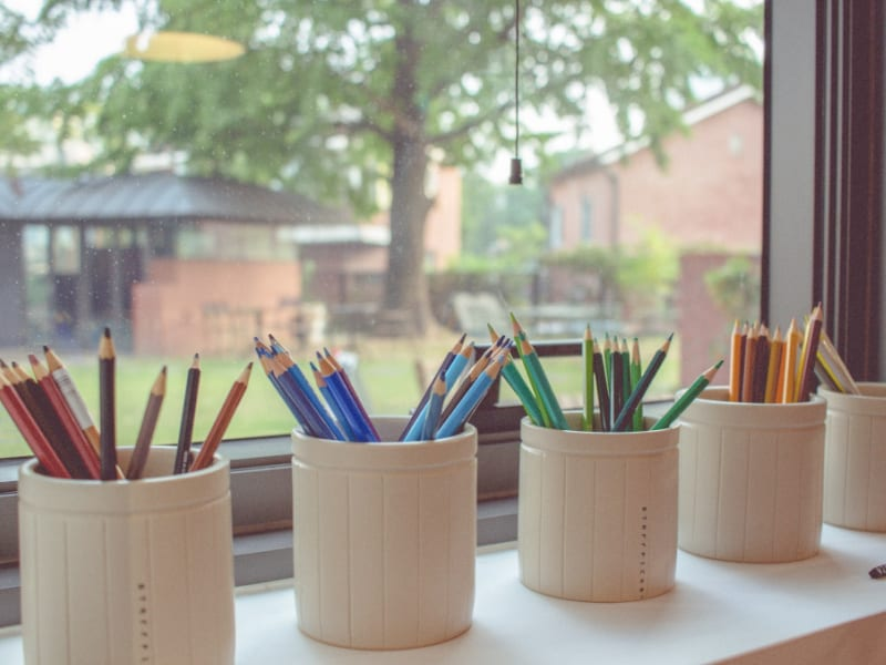 colored pencils in jars by window