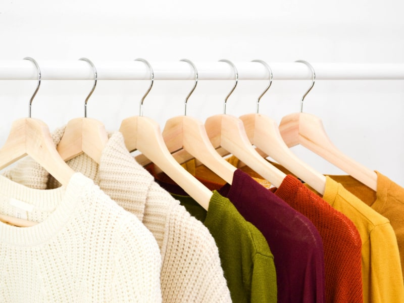 autumn colored sweaters hanging on wood hangers