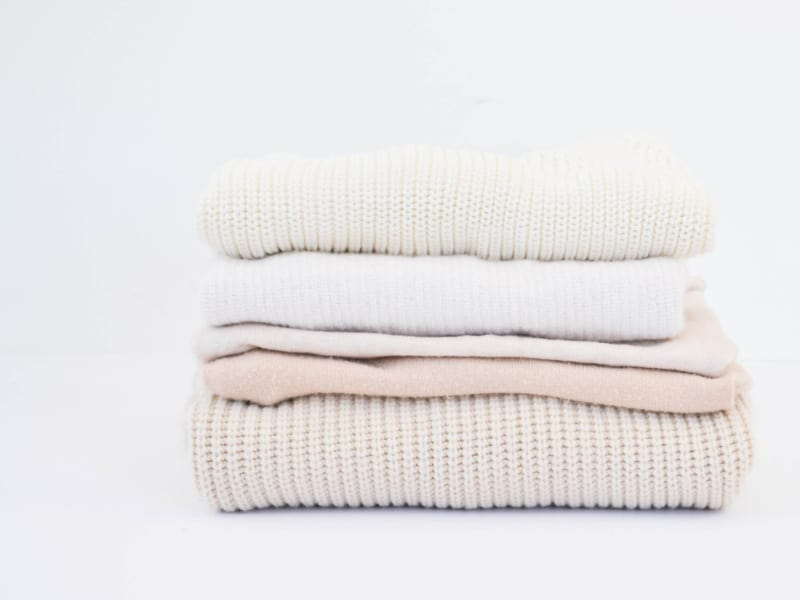 stack of neatly folded tan and cream sweaters