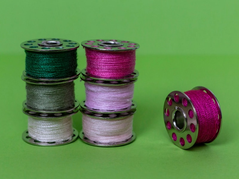 stacks of thread bobbins on green background