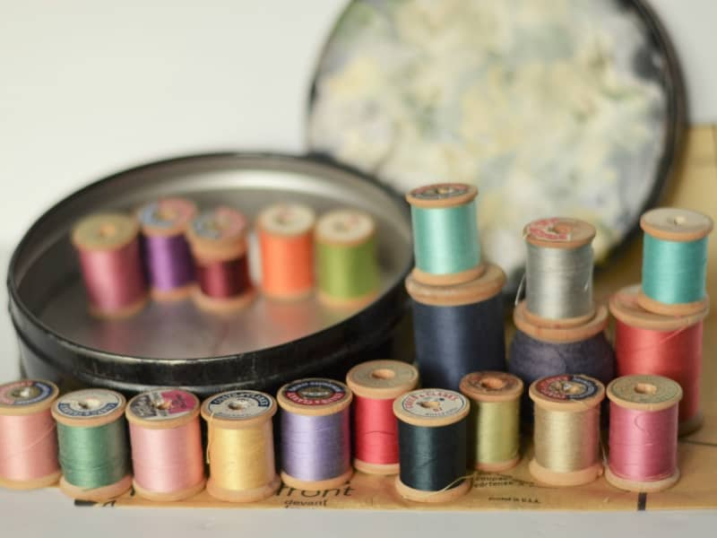 vintage wood thread spools in round tin can