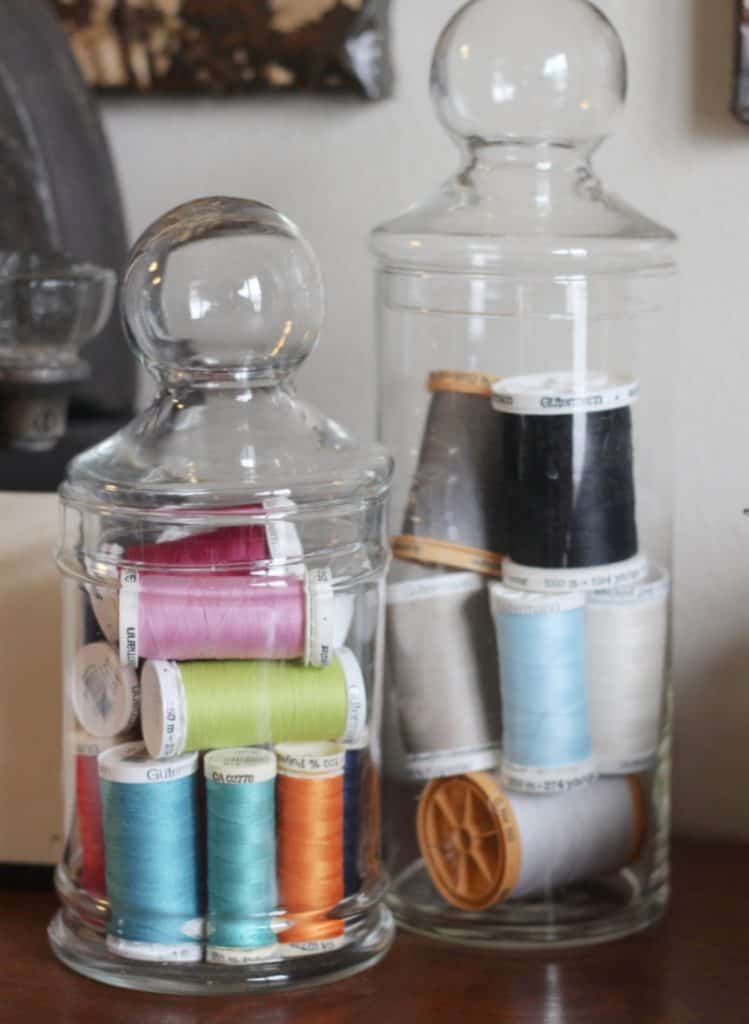 colorful spools of thread in glass jars