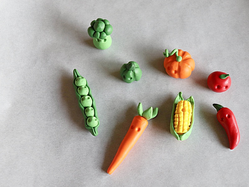 8 small clay veggie characters with no eyes but dents for eye placement