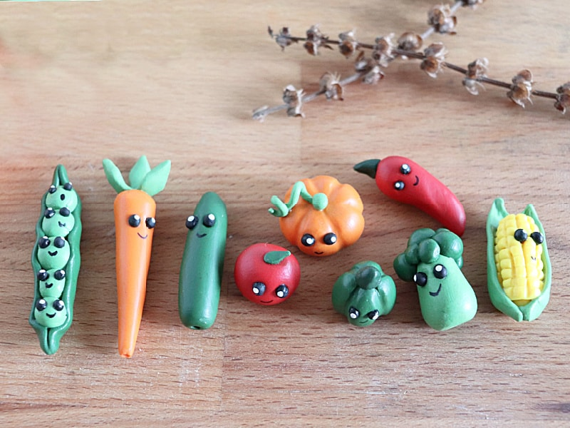 9 tiny clay veggie characters on wood table with branches in background