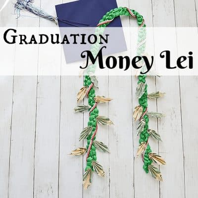money lei and graduation cap on white wood table
