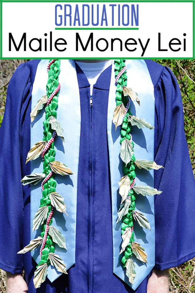 person in blue graduation gown with money lei