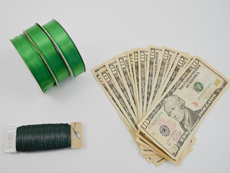 3 rolls of green ribbon, stack of 10 dollar bills and spool of floral wire
