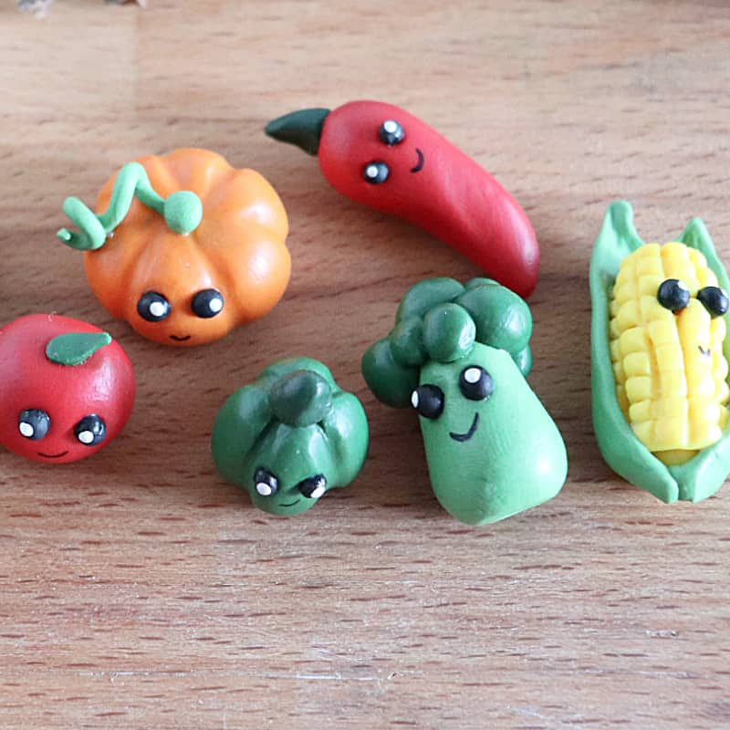 close up of 6 clay veggie crafts with faces on wood table