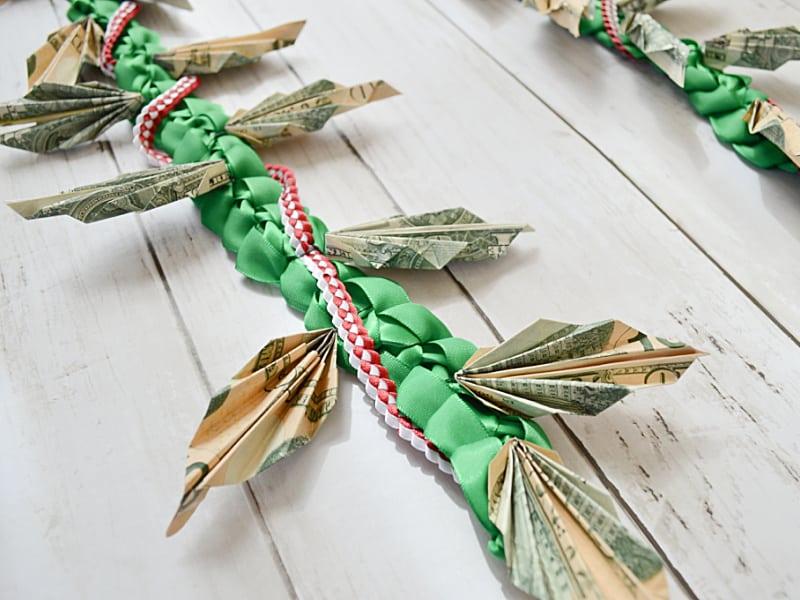 close up of folded money leaves on money lei