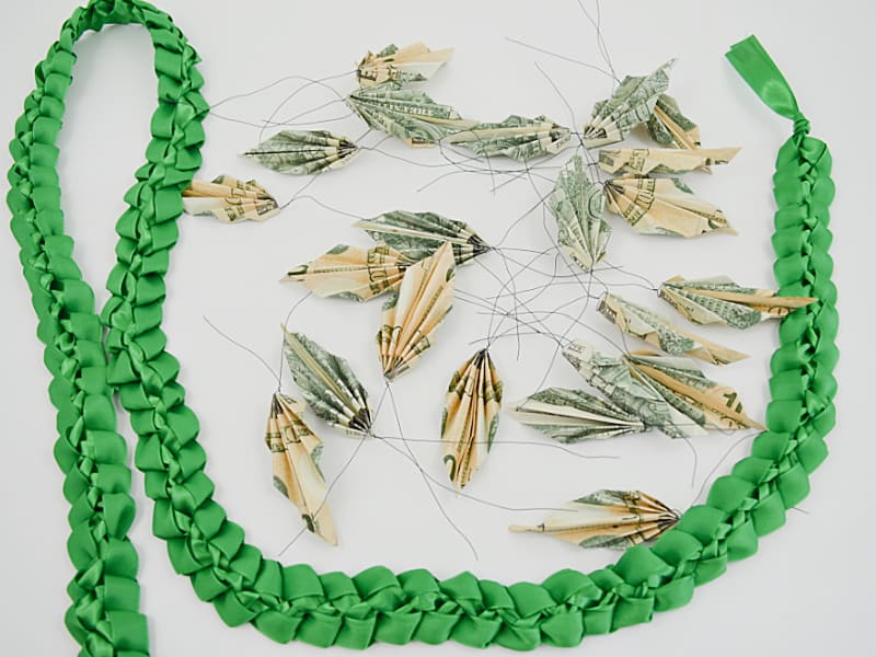 green ribbon lei with folded money leaves scattered near by