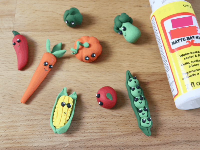 8 different small clay vegetables laying on wood table next to large decoupage glue bottle