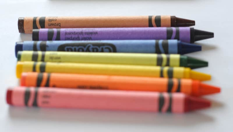 row of colorful crayons on white table
