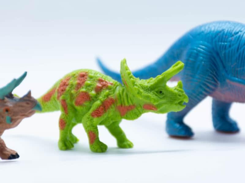 close up of 3 plastic dinosaur toys