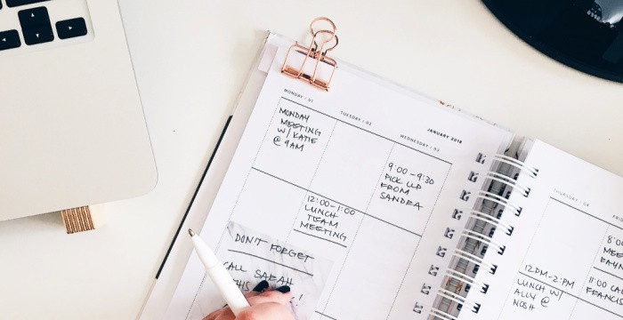 hand holding pen on planner with gold clip on desk