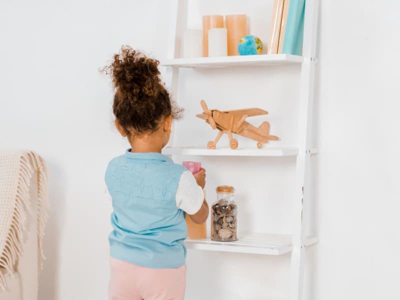young girl placing toys on wall shelf