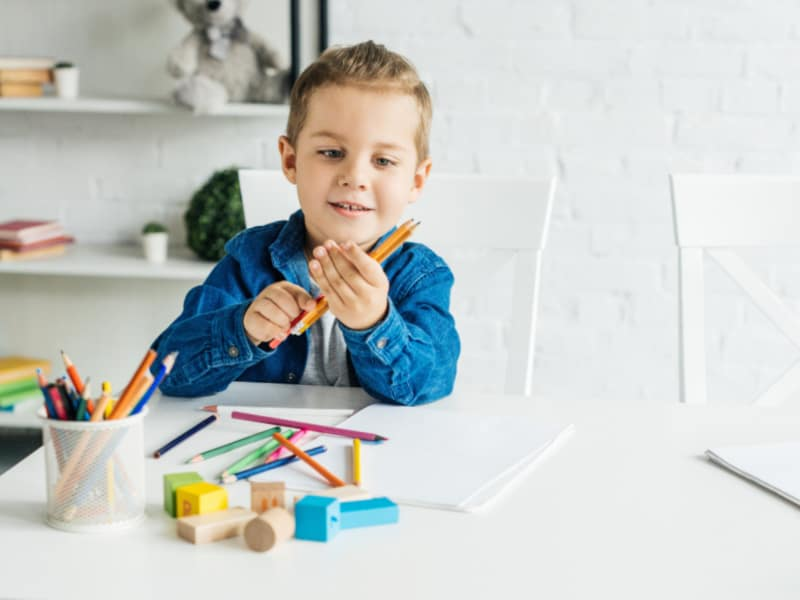 young boy playing at table with shelf of toys behind