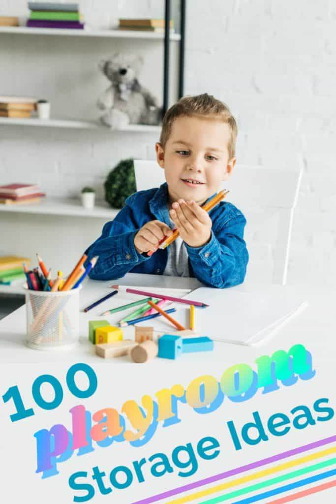 young boy at table in toy room with pencils in hand
