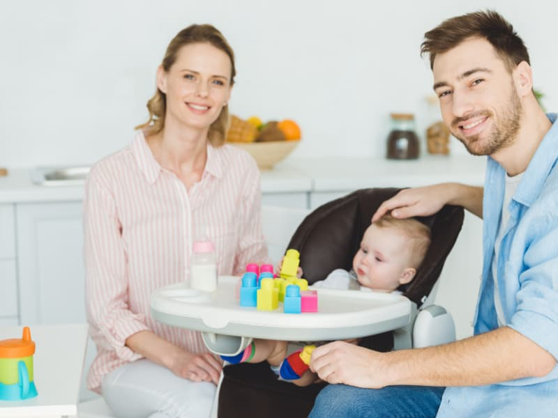 infant in high chair with smiling parents