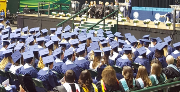 graduation ceremony with graduates in blue cap and gowns