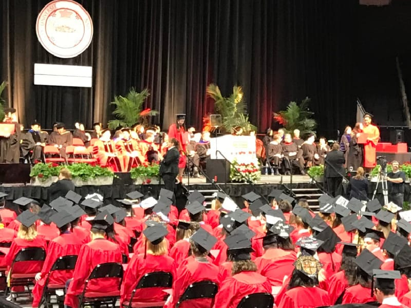 graduation ceremony with graduates in red cap and gowns