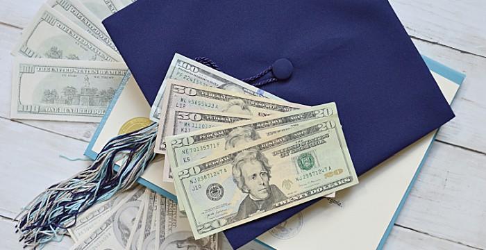 blue graduation cap with cash fanned out