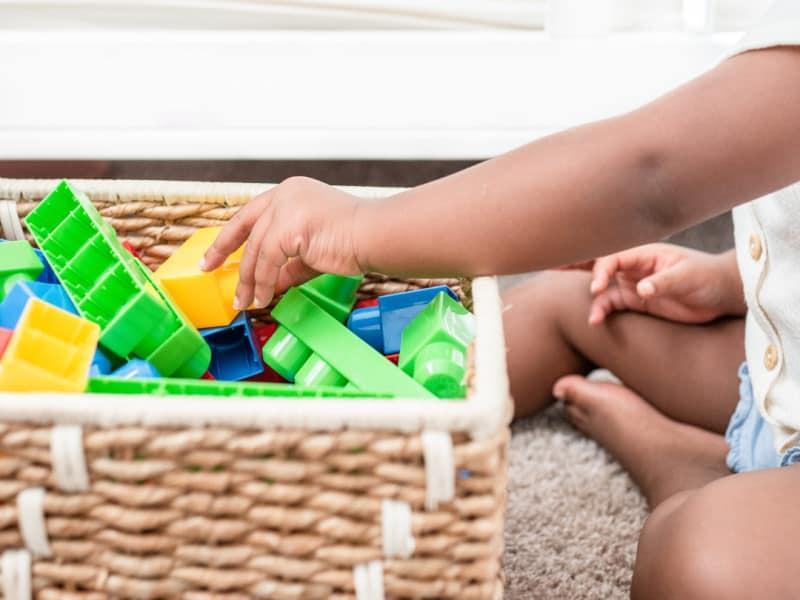 child putting blocks into wicker basket
