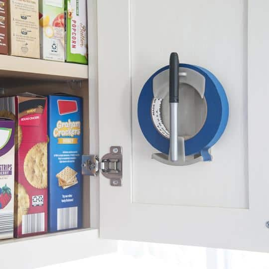 Roll of blue painter's tape and marker hanging on inside of kitchen cabinet door