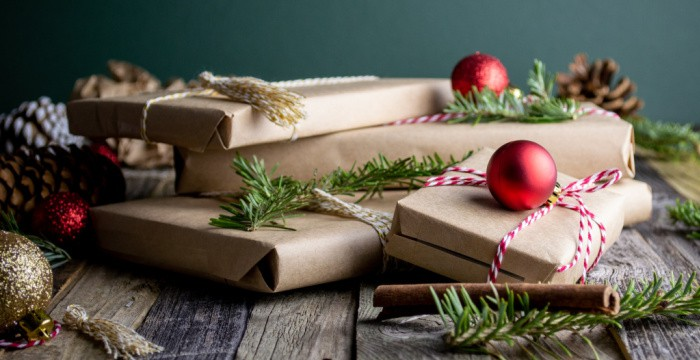 gifts wrapped in brown paper with greenery and red ornaments attached