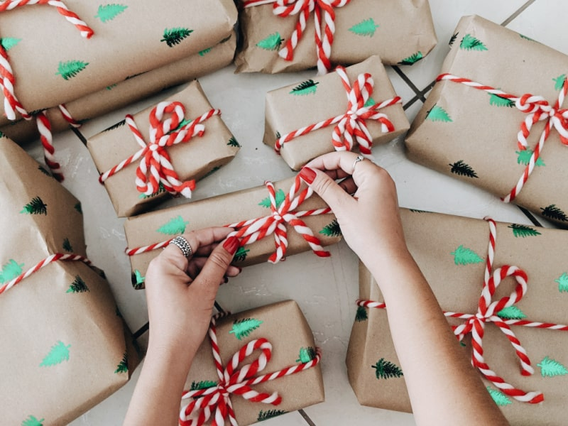 hands tying red and white bow on package in pile of packages wrapped in brown paper