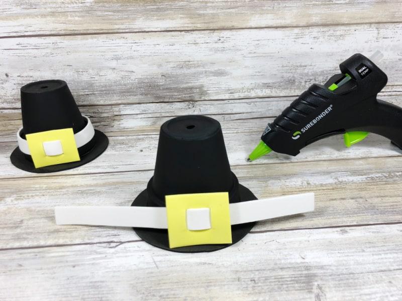 glue gun next to 2 crafted pilgrim hat
