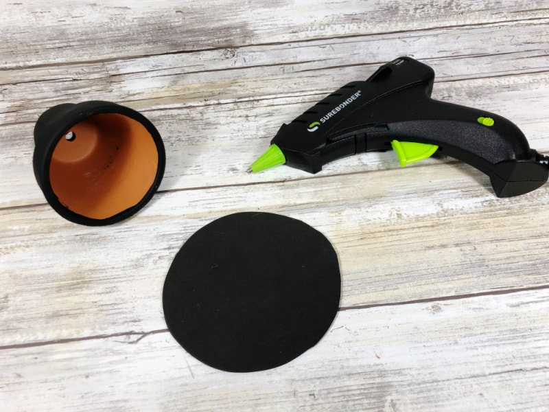 small clay pot painted black with glue gun near by
