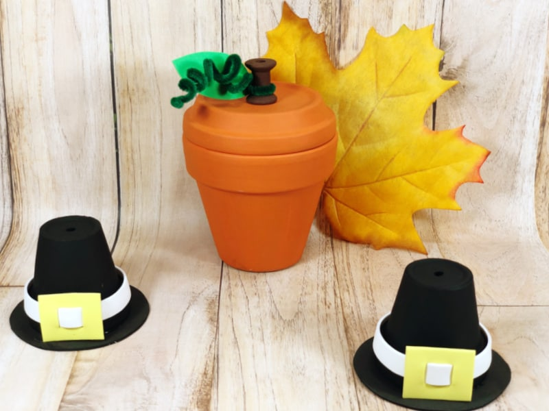 crafted clay pot pumpkin with 2 crafted pilgrim hats in front